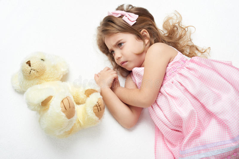 Angry girl child with teddy bear lie on white towel in bed, dressed in pink stock images