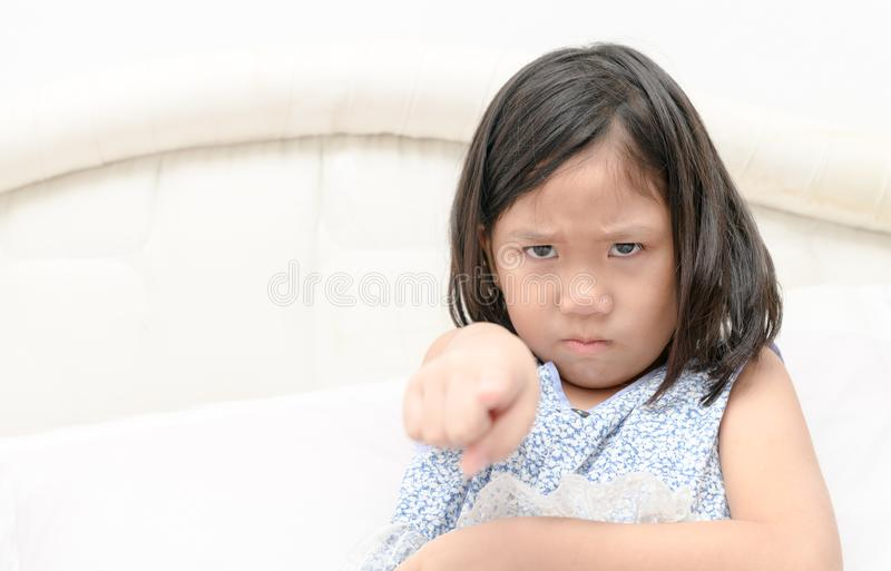 Angry girl pointing finger at someone displeased. royalty free stock photo