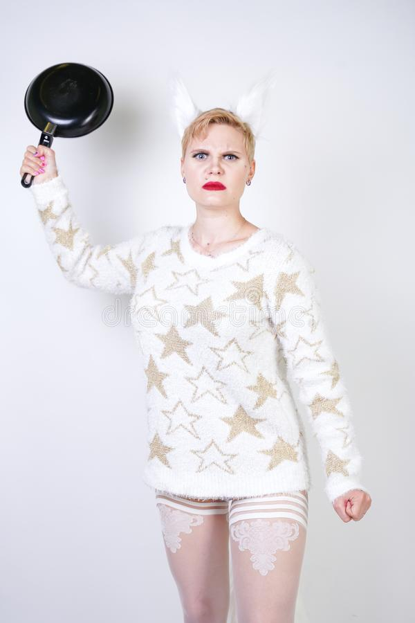 An angry girl with short blonde hair in a fluffy sweater with fur ears. evil plus size woman with black empty frying pan in hand o stock photos