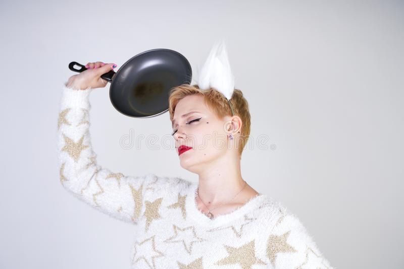 An angry girl with short blonde hair in a fluffy sweater with fur ears. evil plus size woman with black empty frying pan in hand o stock image
