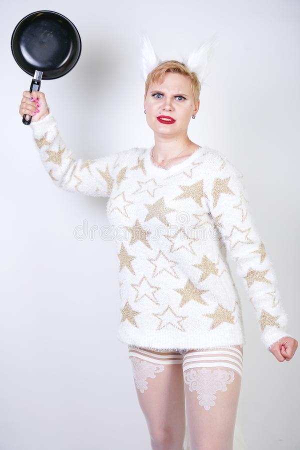 An angry girl with short blonde hair in a fluffy sweater with fur ears. evil plus size woman with black empty frying pan in hand o royalty free stock photography