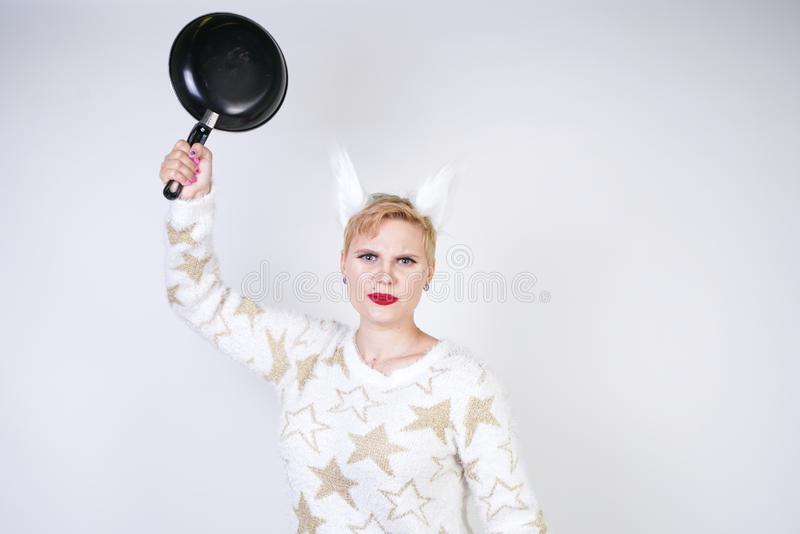 An angry girl with short blonde hair in a fluffy sweater with fur ears. evil plus size woman with black empty frying pan in hand o royalty free stock images