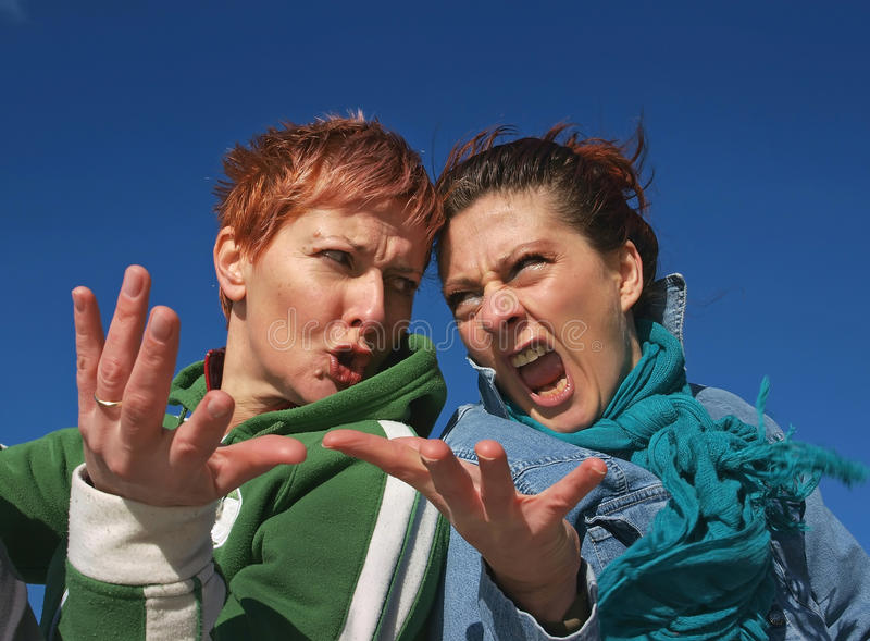 Angry girls having quarrel. Two woman of scowling and angry faces, (pissed off) they are fight and argue fiercely gesturing hands. Horizontal color photo royalty free stock photography