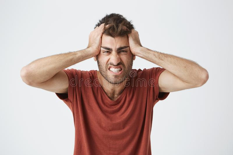 Angry good-looking caucasian male in red t-shirt having mad expressions, squeezing head with hands of people. Around on work. Negative emotions royalty free stock images