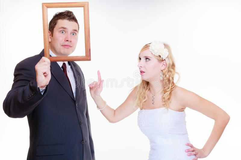 Angry groom and bride holding empty frame. Wedding day, negative relationship concept. Groom and bride holding, posing with empty photo frame having bad argument royalty free stock image