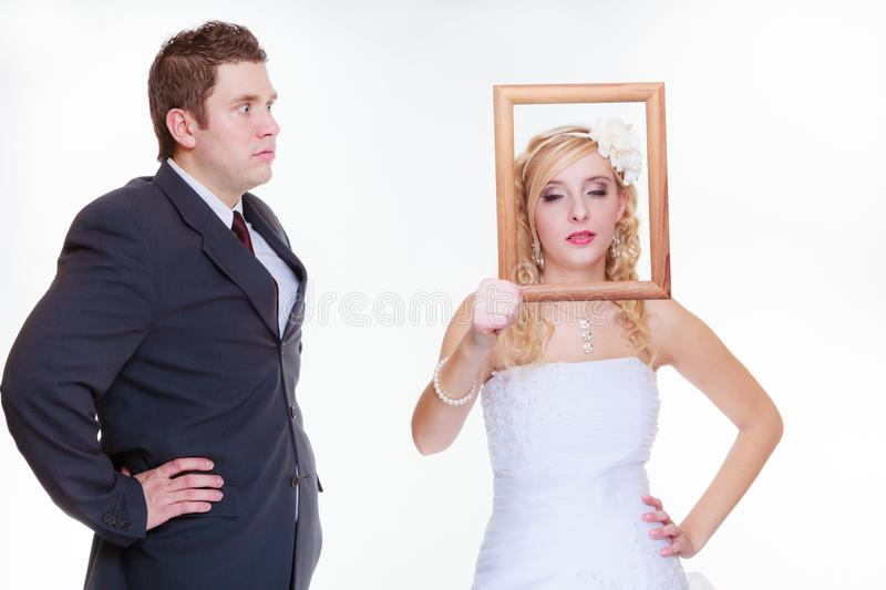 Angry groom and bride holding empty frame. Wedding day, negative relationship concept. Groom and bride holding, posing with empty photo frame having bad argument stock image