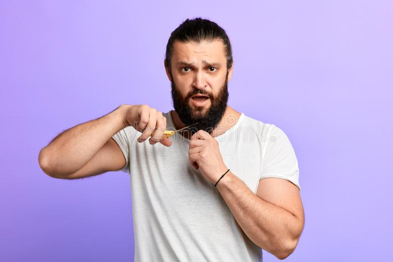 Angry handsome man cutting his beard stock images