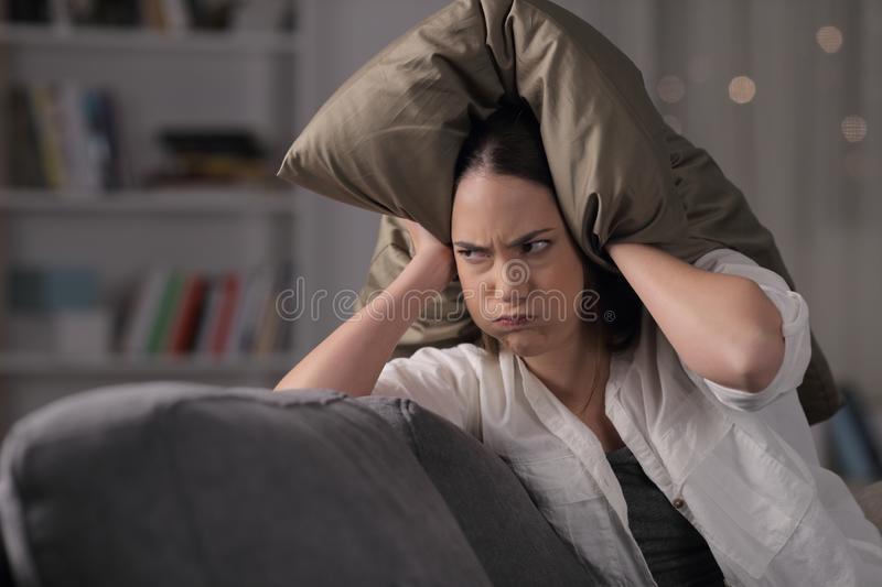Angry homeowner suffering neighbor noise covering ears. Sitting on a couch in the night at home royalty free stock photography