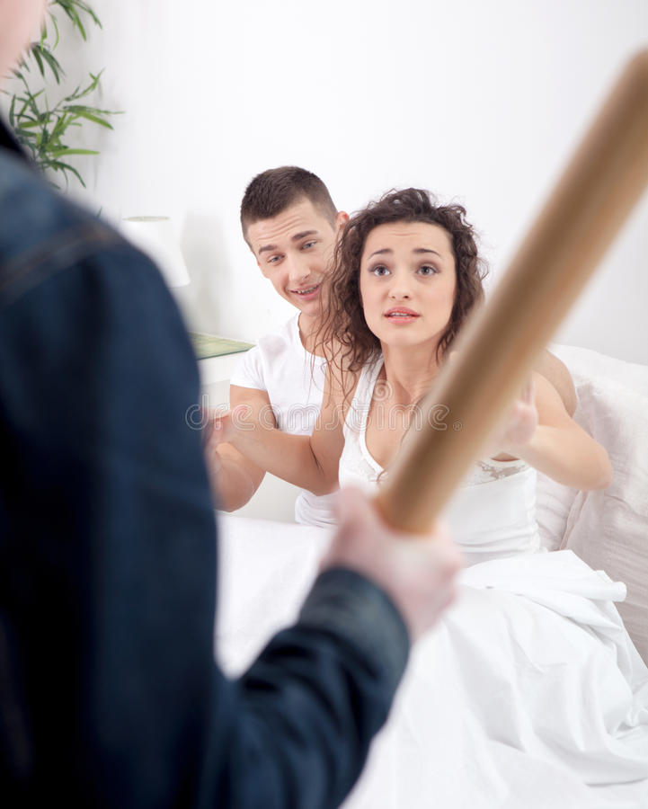 Angry husband with baseball bat caught cheating wife with lover. Angry husband holding the baseball bat, a women and a men beg for mercy royalty free stock photo