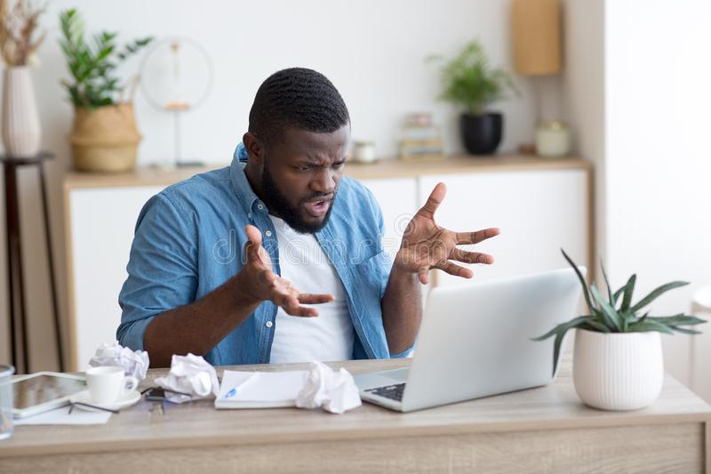 Angry and irritated entrepreneur with a laptop in office or home royalty free stock photography