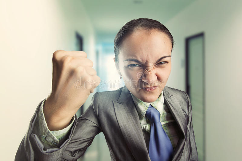 Angry irritated woman in the office. Angry irritated woman clenching her fist in the office royalty free stock photos