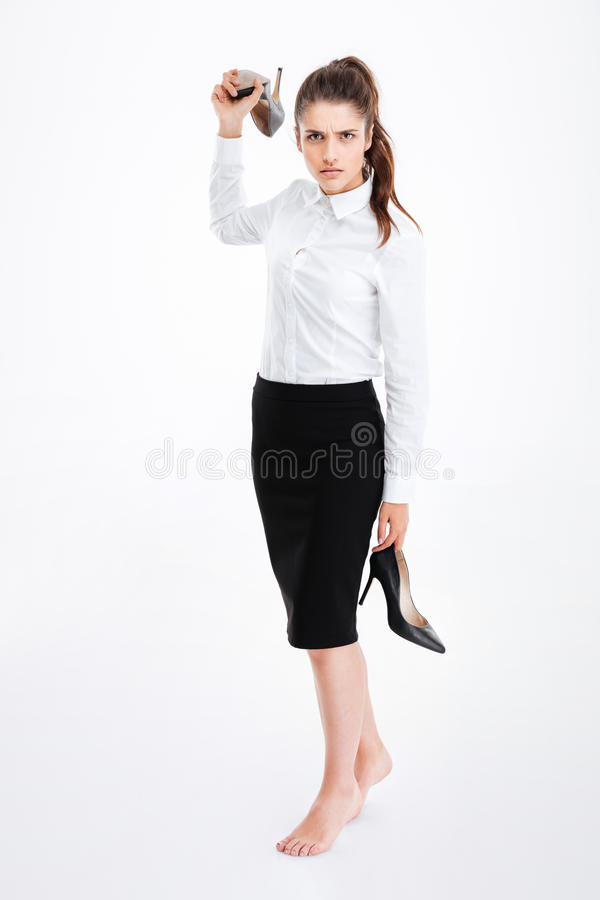 Angry irritated young businesswoman standing and throwing high heels shoes. Over white background royalty free stock photography