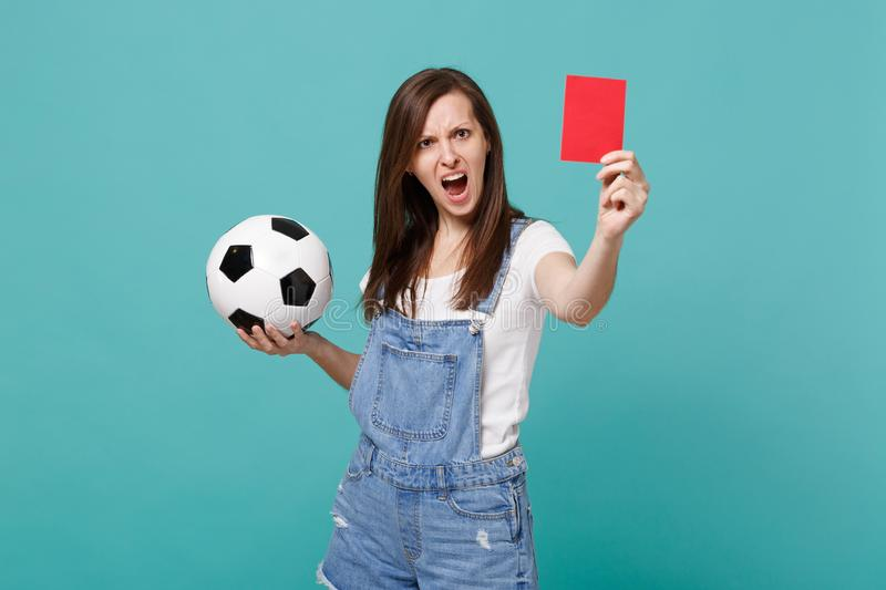 Angry irritated young woman football fan support team with soccer ball, red card, propose player retire from field. Isolated on blue turquoise background stock photos