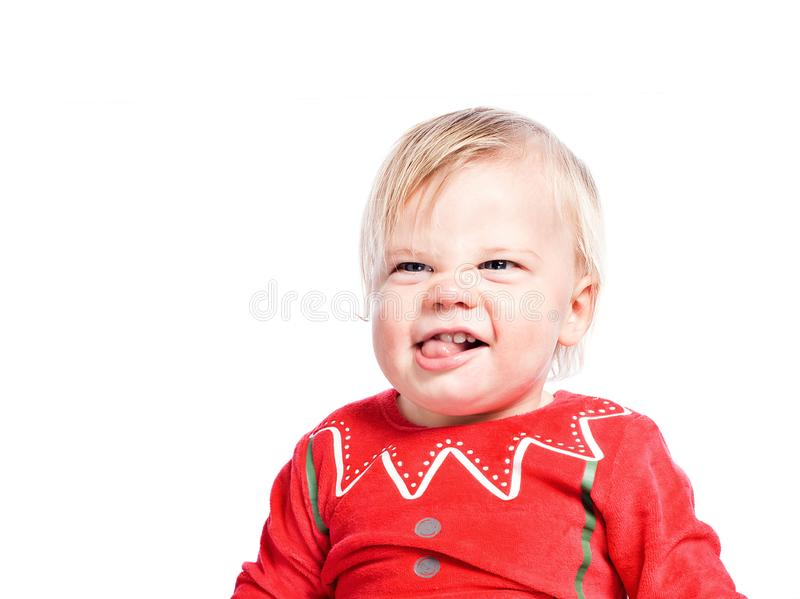 Angry kid. Christmas chores. Close-up of a little boy in a red suit. Grimacing and making faces. Isolated on white background stock photos