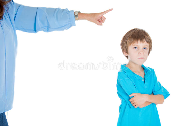 An angry kid confronting his mothers orders. Closeup portrait of parent pointing at child to go to room for misbehaving while kid is upset with arms folded royalty free stock image
