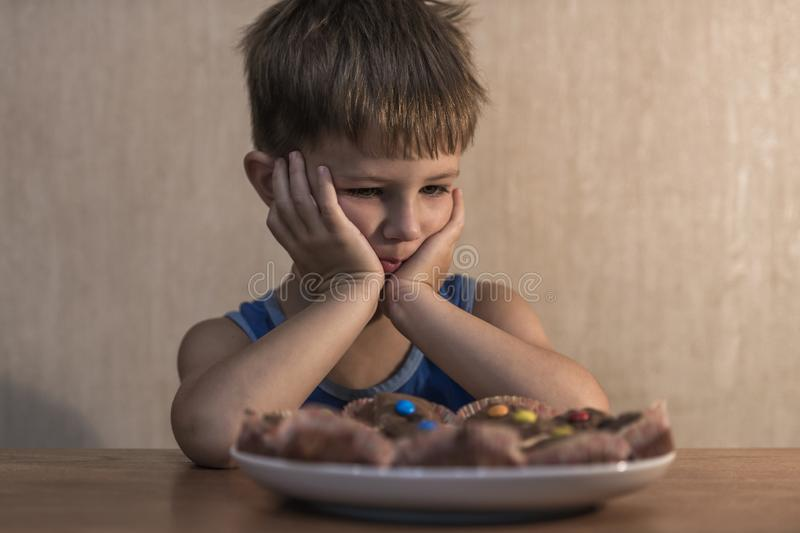 Angry little boy sitting at the dinner table. stock photography