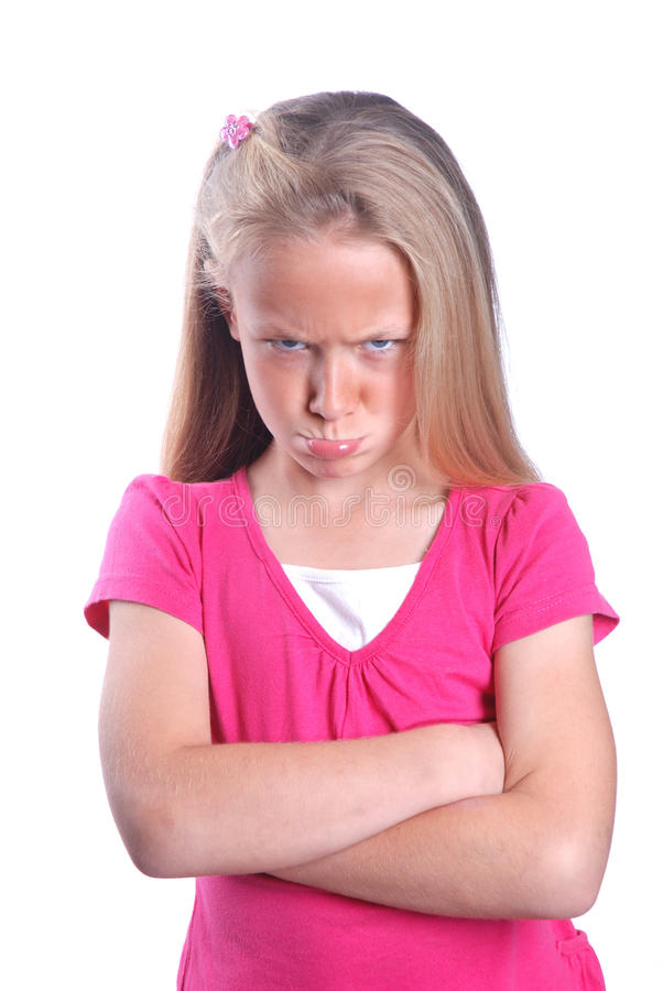 Angry little girl. Portrait of a pretty little Caucasian preteen girl child with angry facial expression and crossed arms in front of her having a tantrum. Image royalty free stock images