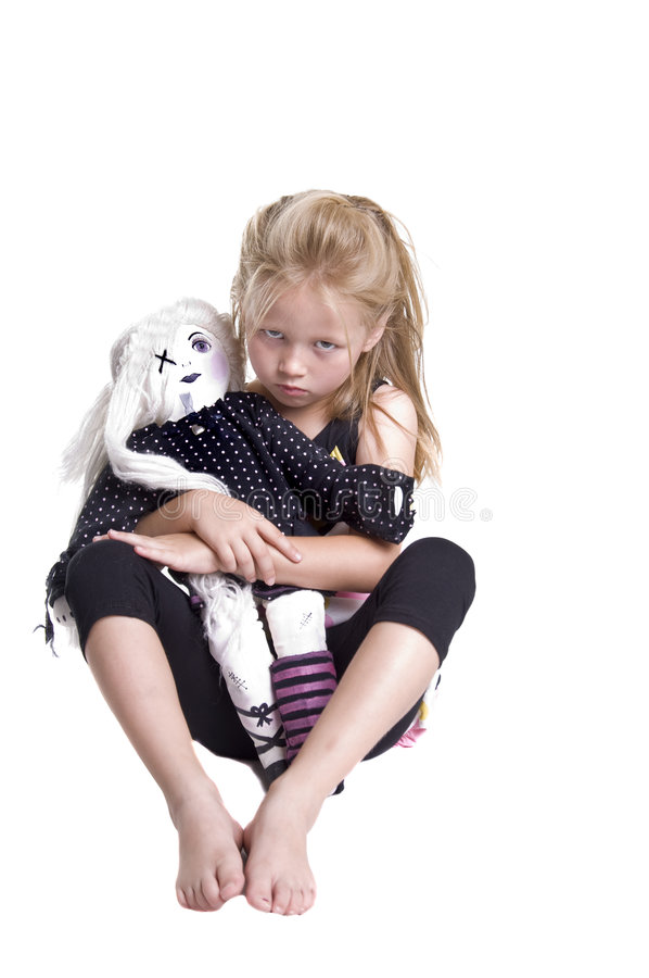 Angry Little Girl. Angry little blonde haired girl sitting barefoot on the floor holding a homemade dolly royalty free stock images