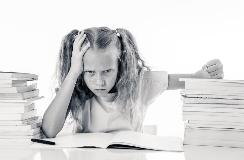 Angry little girl with a negative attitude towards studies and school after studying too much and having too many homework in. Children education concept royalty free stock photography