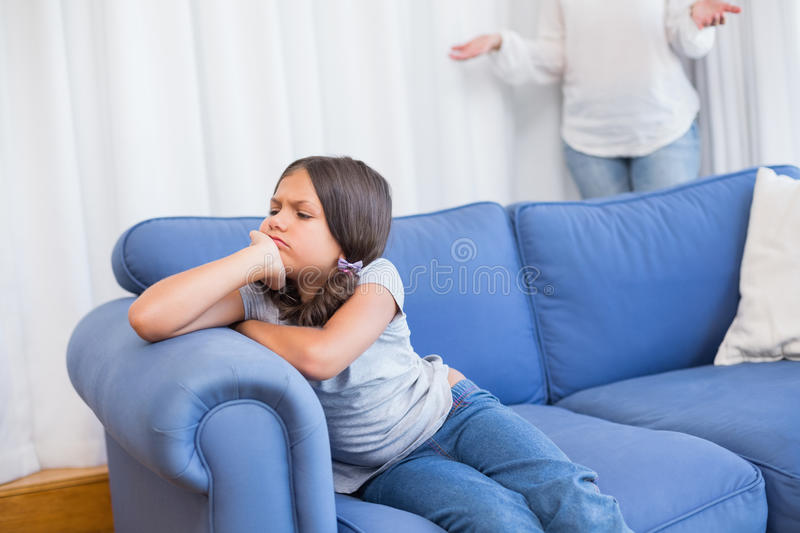 Angry little girl sitting on the couch royalty free stock photography