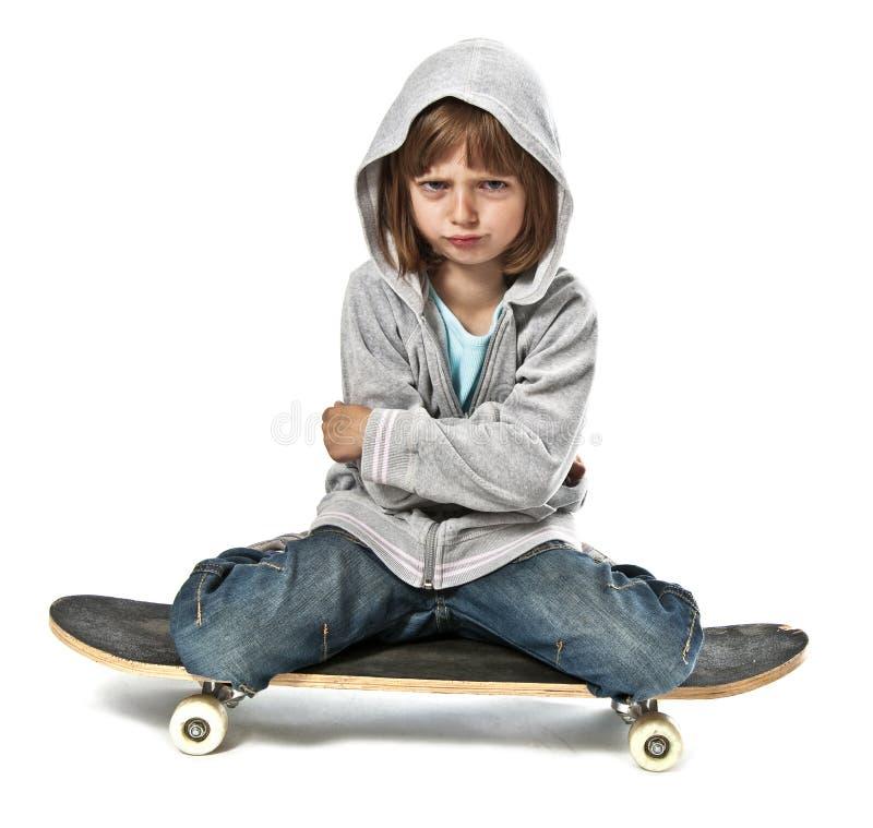Angry little girlsitting onskateboard royalty free stock photos