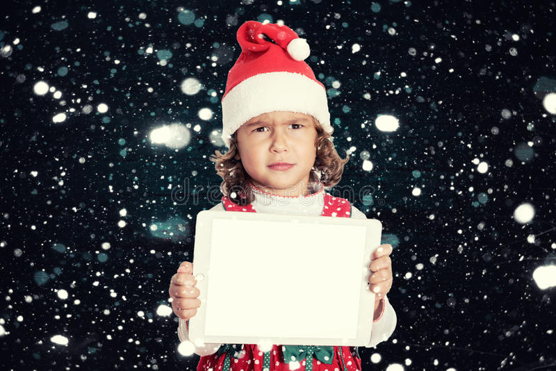 Angry little Santa. Portrait of angry little Santa holding blank screen tablet pc stock photography