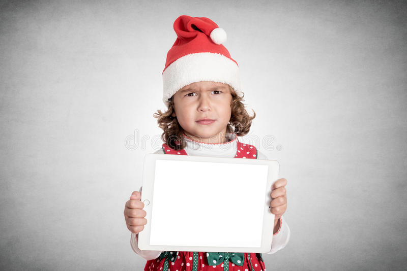 Angry little Santa. Portrait of angry little Santa holding blank screen tablet pc,isolated on white background royalty free stock photo