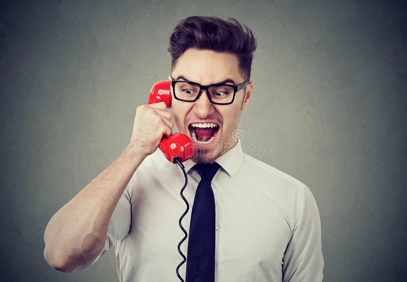 Angry mad businessman screaming on the phone stock image
