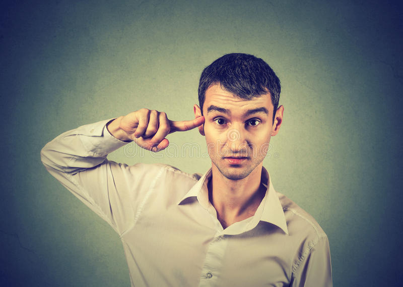 Angry mad man gesturing with finger against temple are you crazy?. Angry mad young man gesturing with his finger against temple asking are you crazy? on gray stock image