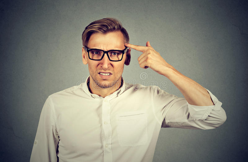 Angry mad man gesturing with finger are you crazy?. Angry mad young man gesturing with finger against temple asking are you crazy? Isolated on gray background stock photo