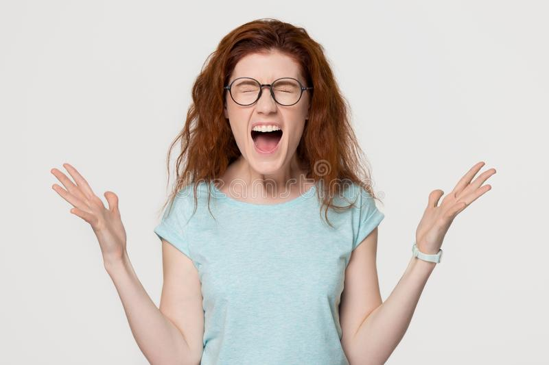 Angry mad redhead hysterical girl yelling shouting isolated on background stock photography