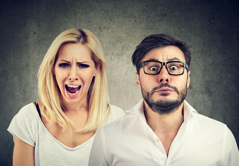 Angry mad woman screaming and fearful man. Angry mad women screaming and fearful stressed funny looking man royalty free stock photography