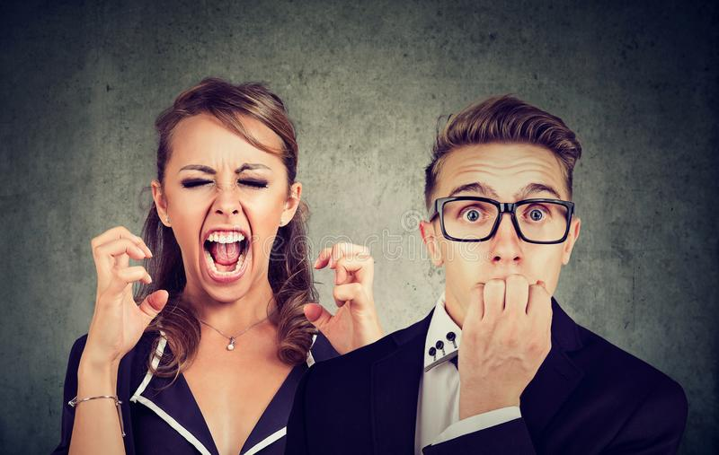 Angry mad woman screaming and fearful man. Angry mad women screaming and fearful stressed young anxious man royalty free stock photo