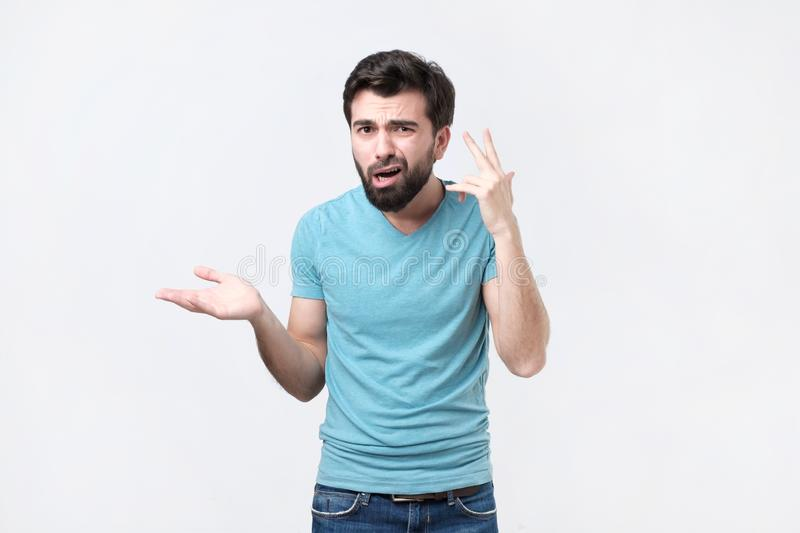 Angry mad young hispanic man gesturing with his finger against temple asking are you crazy. royalty free stock photo