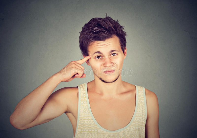 Angry mad young man gesturing with finger are you crazy?. On gray background. Negative emotion facial expression feeling body language stock photos
