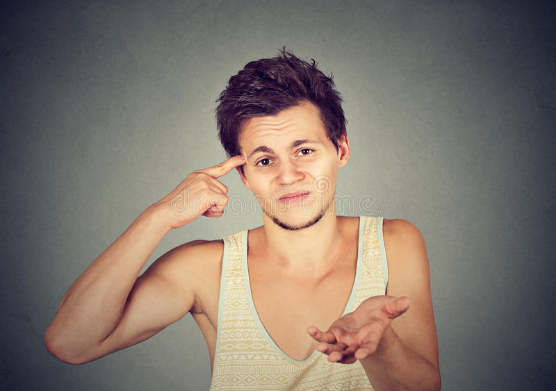 Angry mad young man gesturing with finger are you crazy?. On gray background. Negative emotion facial expression feeling body language stock photo