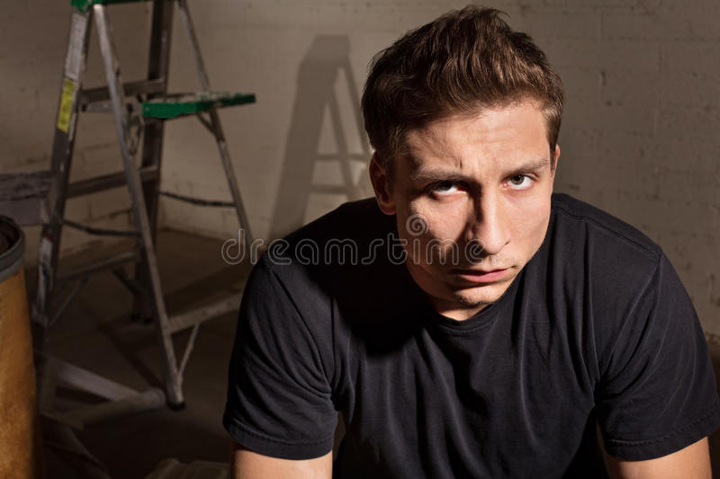 Angry Male with Ladder. Angry young white man with ladder in background stock images