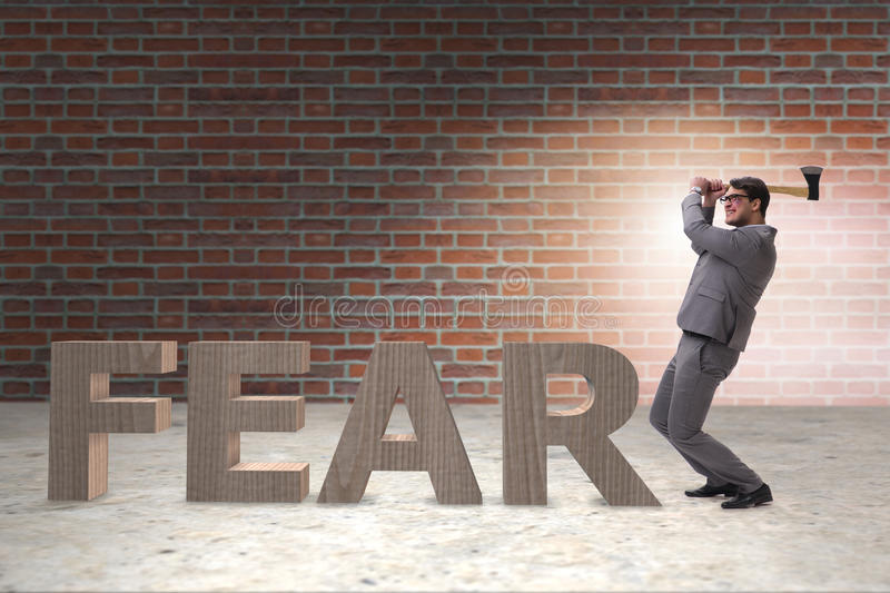 The angry man with axe axing the word fear. Angry man with axe axing the word fear stock image