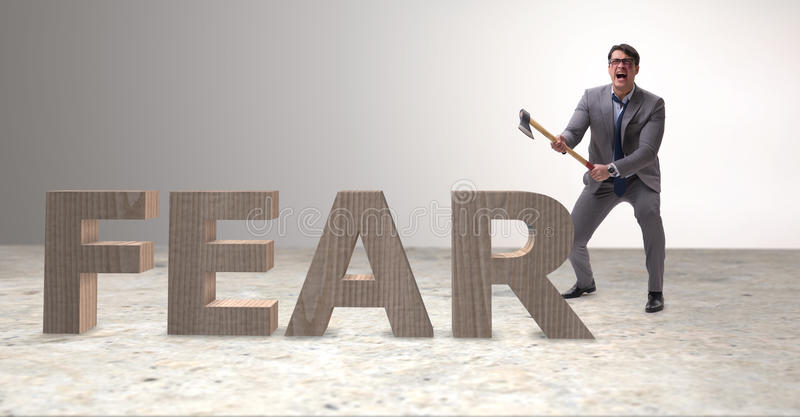 The angry man with axe axing the word fear. Angry man with axe axing the word fear royalty free stock photos
