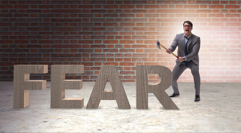 The angry man with axe axing the word fear. Angry man with axe axing the word fear stock photo