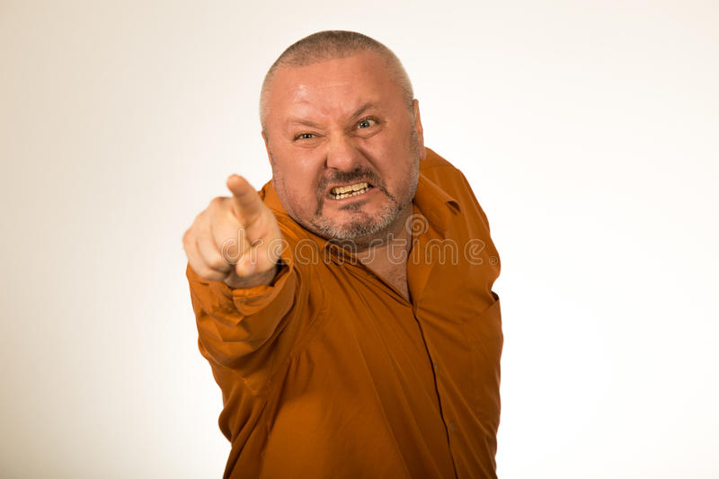 Angry man with a beard baring his teeth and snarling at the camera. With pointed finger at you stock photo
