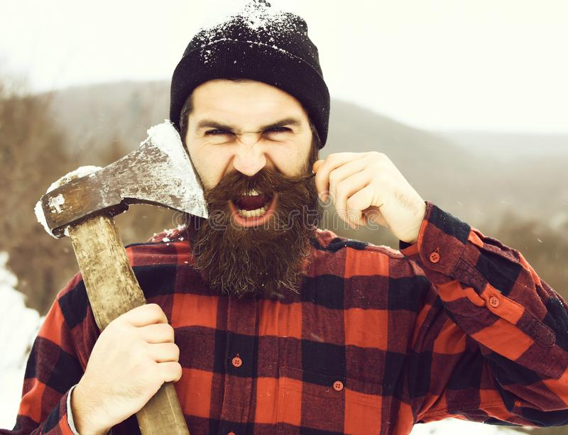 Angry man or brutal lumberjack. Bearded hipster, with beard and moustache in red checkered shirt shaves with axe blade in snowy forest on winter day outdoors stock images