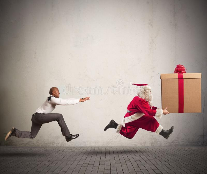 Angry man chasing Santa Claus royalty free stock photo