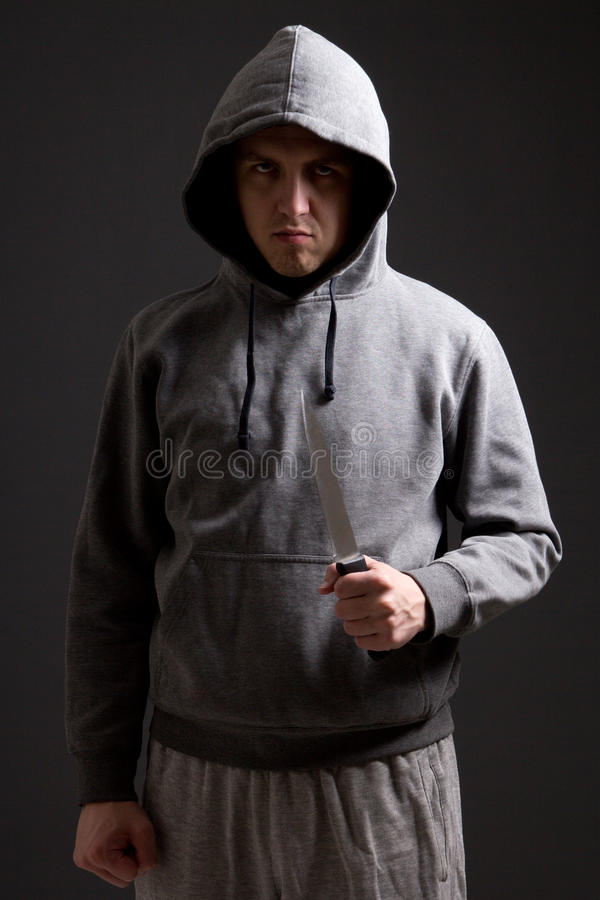 Angry man criminal with knife over grey royalty free stock photography