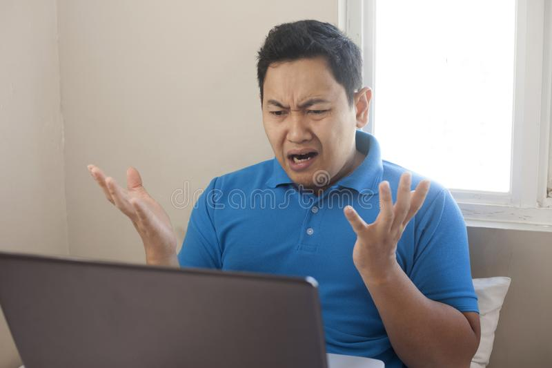 Angry Man Disappointed Expression Looking at Laptop. Portrait of young Asian man looked angry or diappointed looking at laptop, upset to see bad business report stock photography