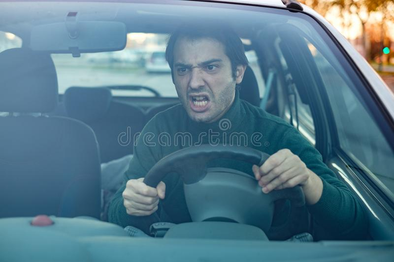 Angry man driver off by drivers in front of him and gestu. Closeup portrait of aggressive male driver honking in traffic jam royalty free stock photos