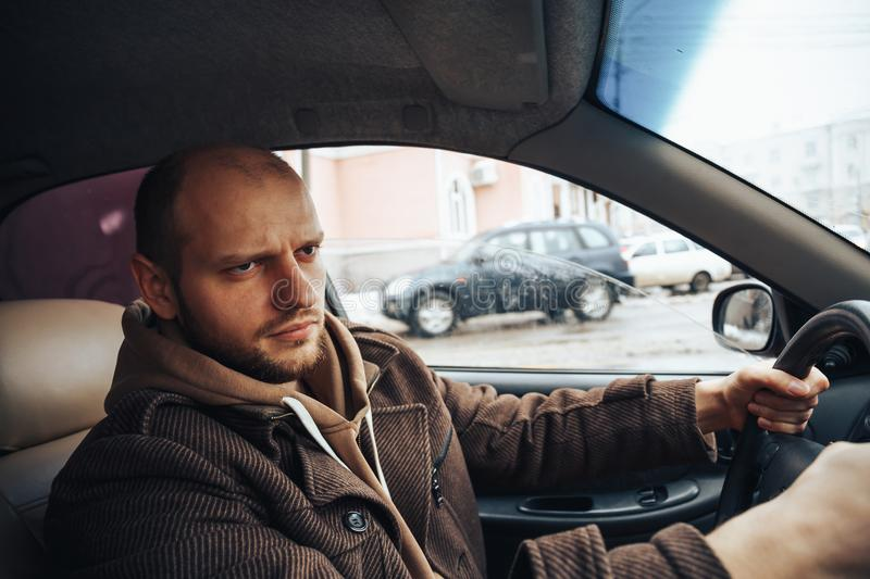 Angry man driving his car, stress on road concept stock images