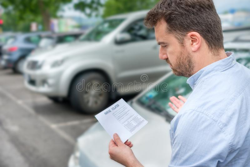 Angry man finding parking ticket fine on his car. Angry man looking on parking ticket placed under windshield wiper royalty free stock images