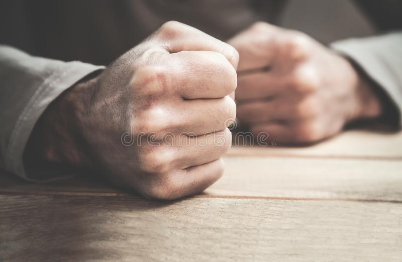 Angry man fists in the table. Business concept stock photo