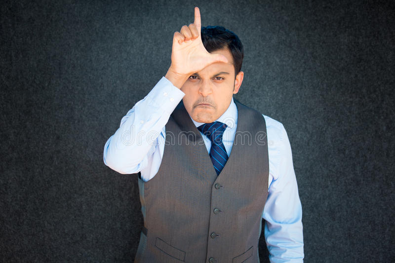 Angry man gesturing you are a loser. Closeup portrait, funny young man in vest and tie displaying loser sign on forehead, looking at you with disgust, gray black stock photo